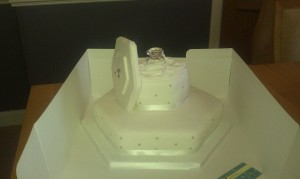 Engagment hexagonal cake box cake with lid with diamond ring keep sake on top. Quote celebration 62